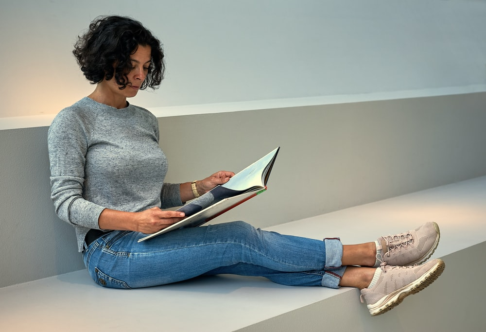 woman in gray sweater and blue denim jeans sitting on white table