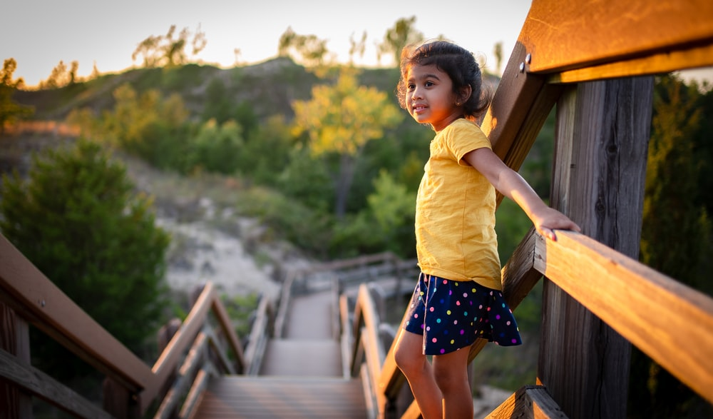 girl in yellow shirt and black and white skirt standing on brown wooden bridge during daytime