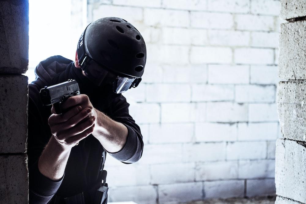 man in black helmet holding black smartphone