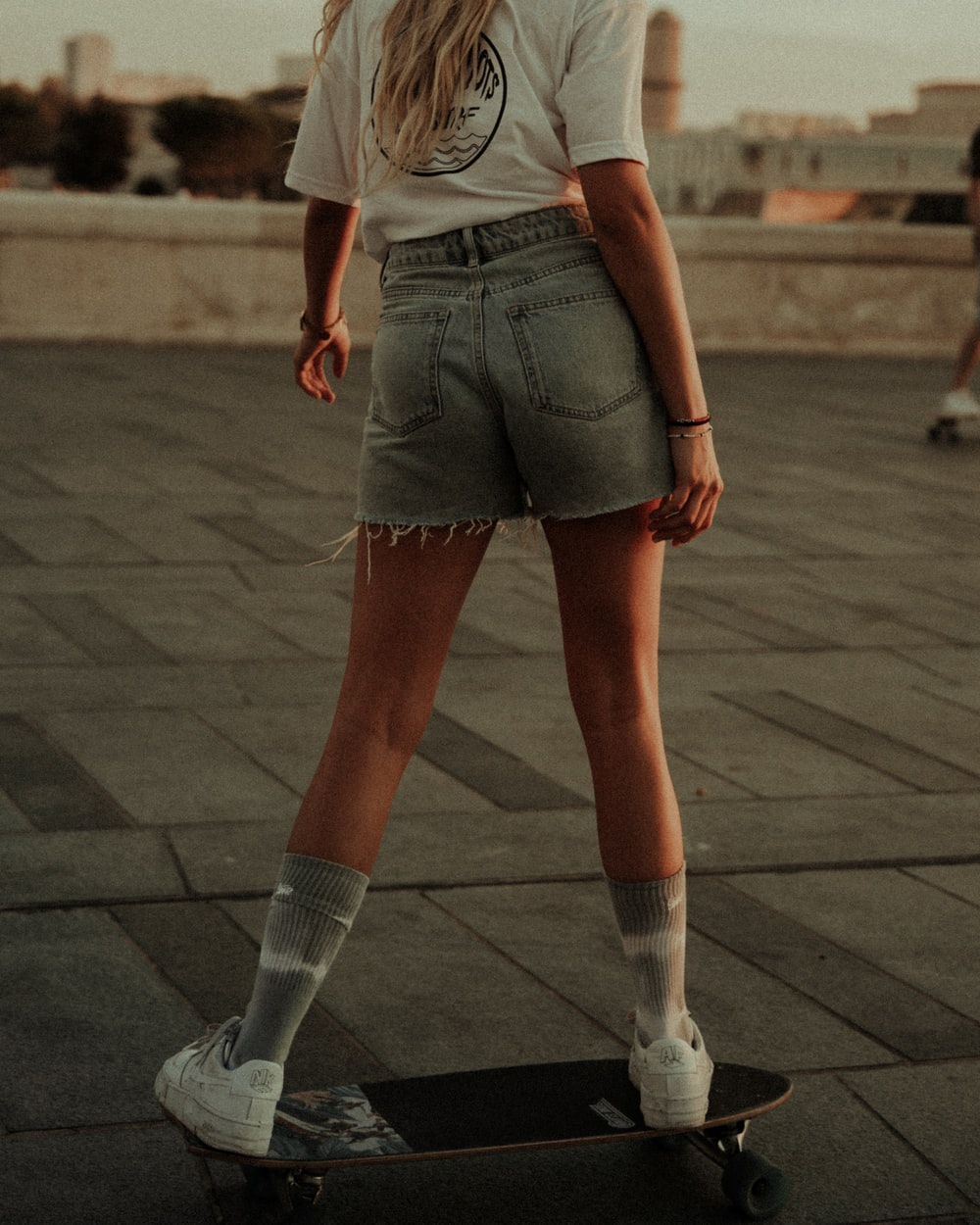 woman in blue denim shorts and white shirt standing on brown concrete floor during daytime