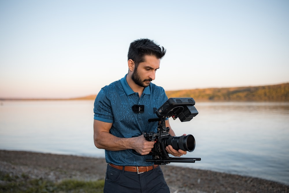 man in blue polo shirt holding black dslr camera standing on brown sand near body of during