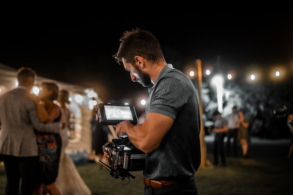 man in blue t-shirt holding black and silver camera