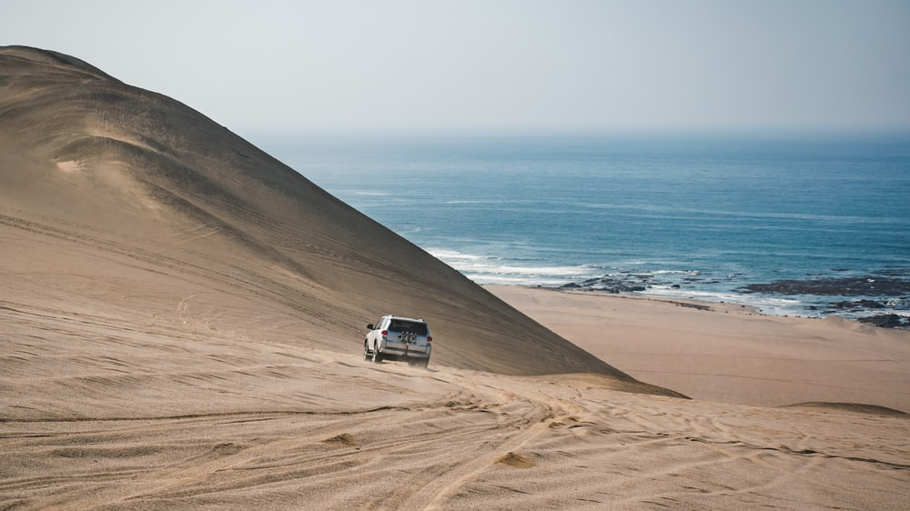 white car on brown sand near body of water during daytime