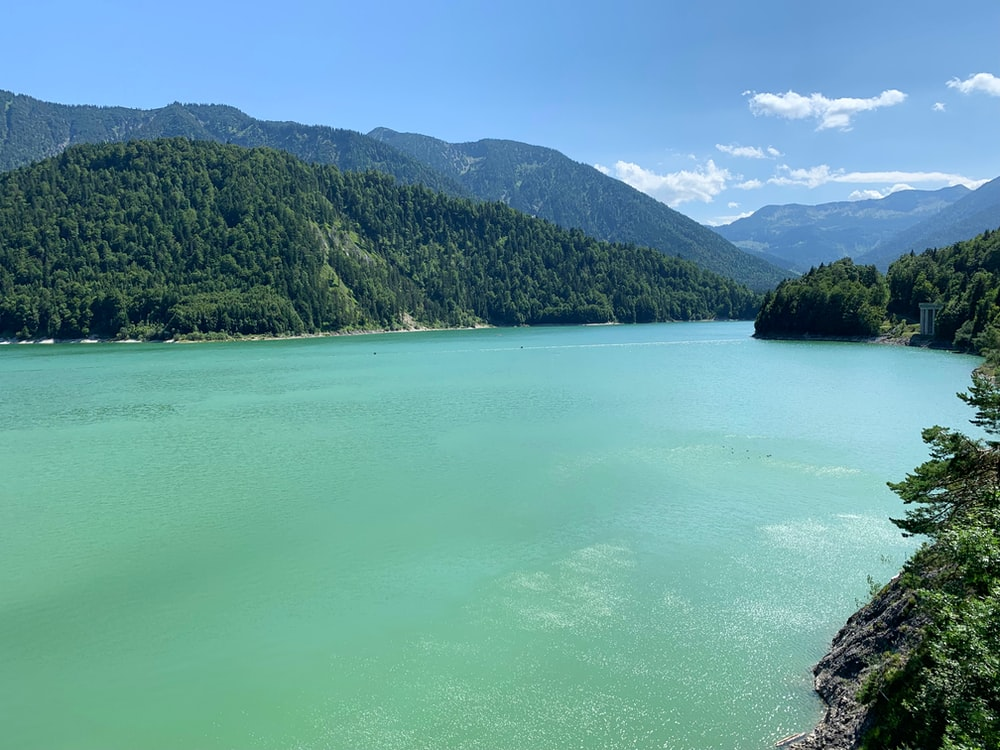 green lake surrounded by green mountains during daytime