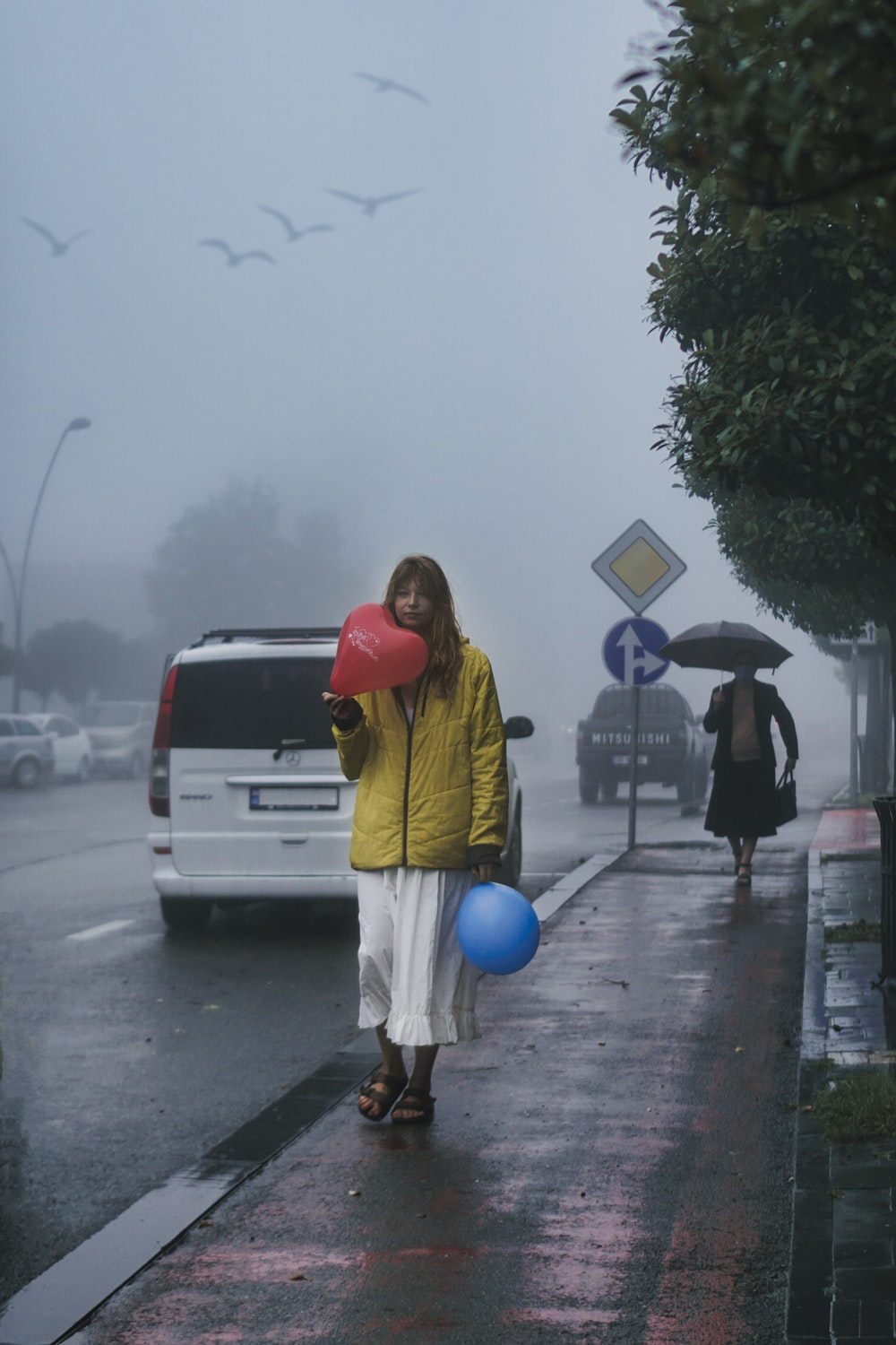 woman in yellow jacket holding blue balloon