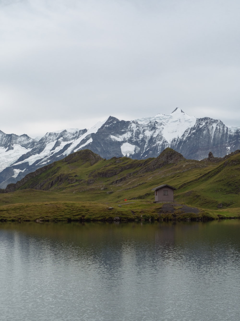 brown wooden house on lake near snow covered mountain