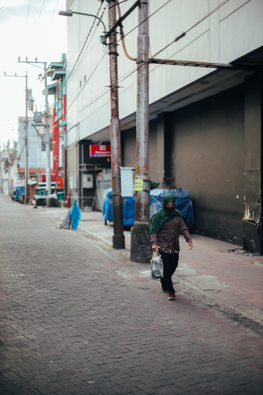 person in green jacket walking on sidewalk during daytime