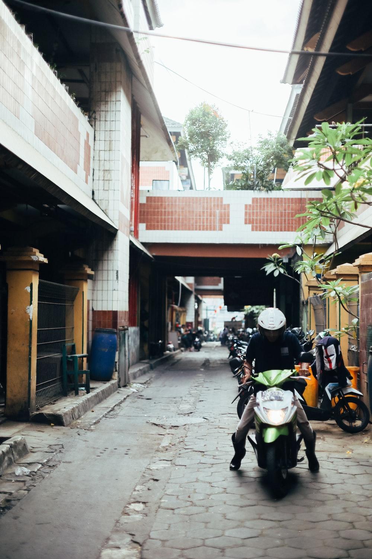 man in black jacket riding on yellow motorcycle during daytime