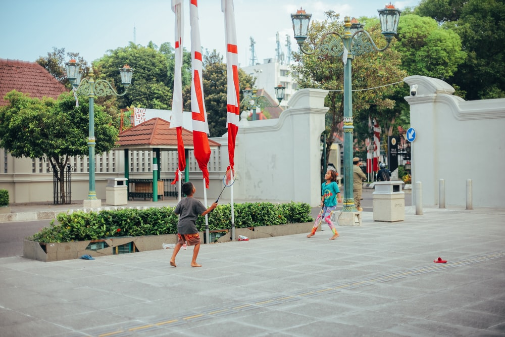 man in black t-shirt and red shorts holding flag of us a during daytime