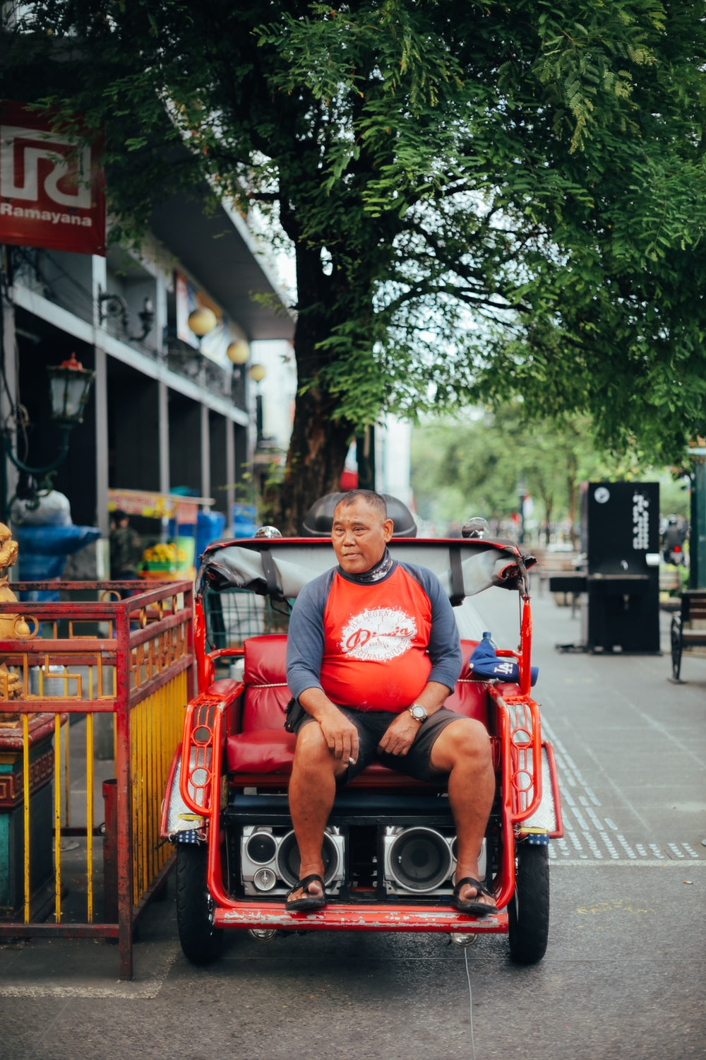 man in red crew neck t-shirt sitting on red wooden bench during daytime