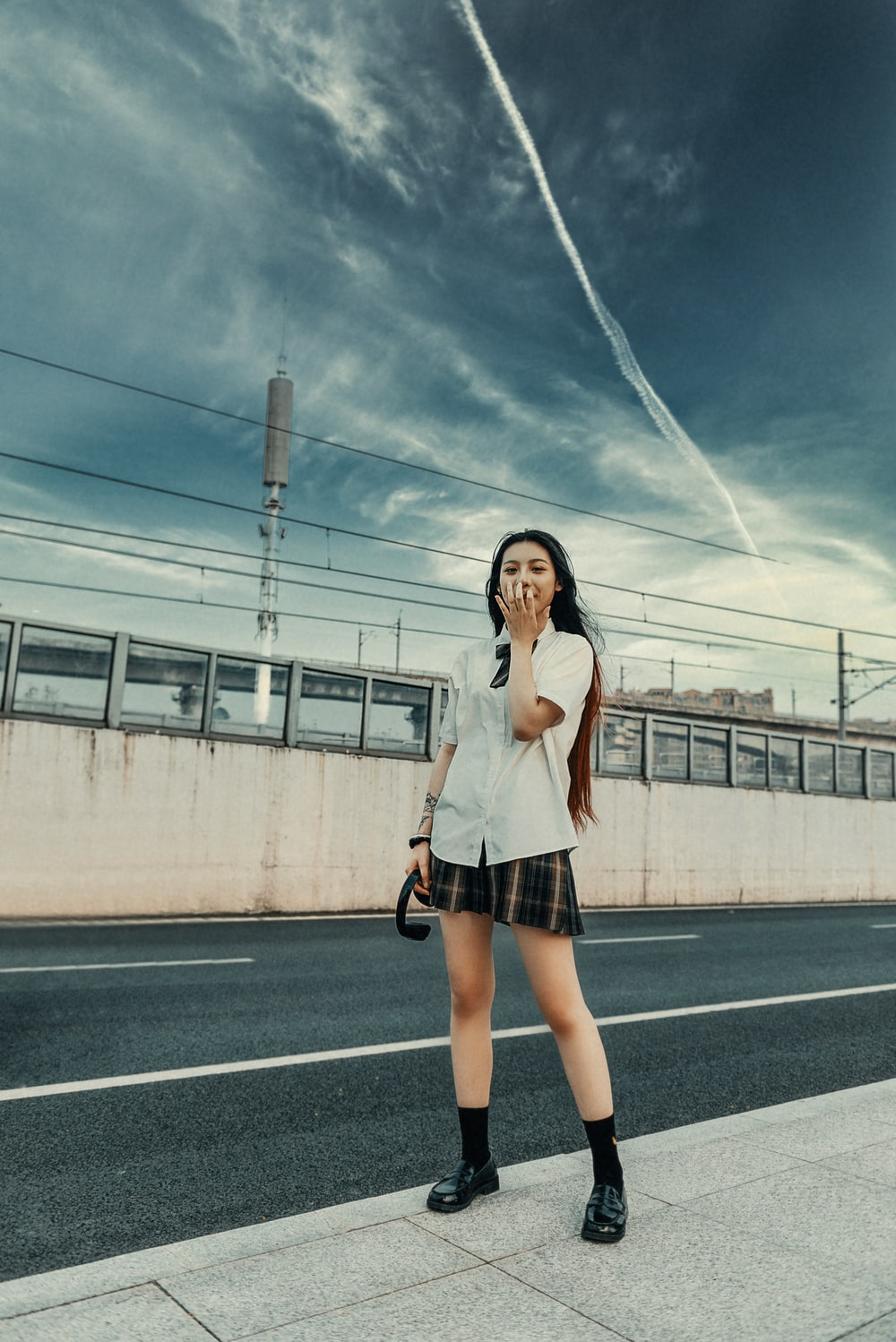 woman in white shirt and black skirt standing on road during daytime