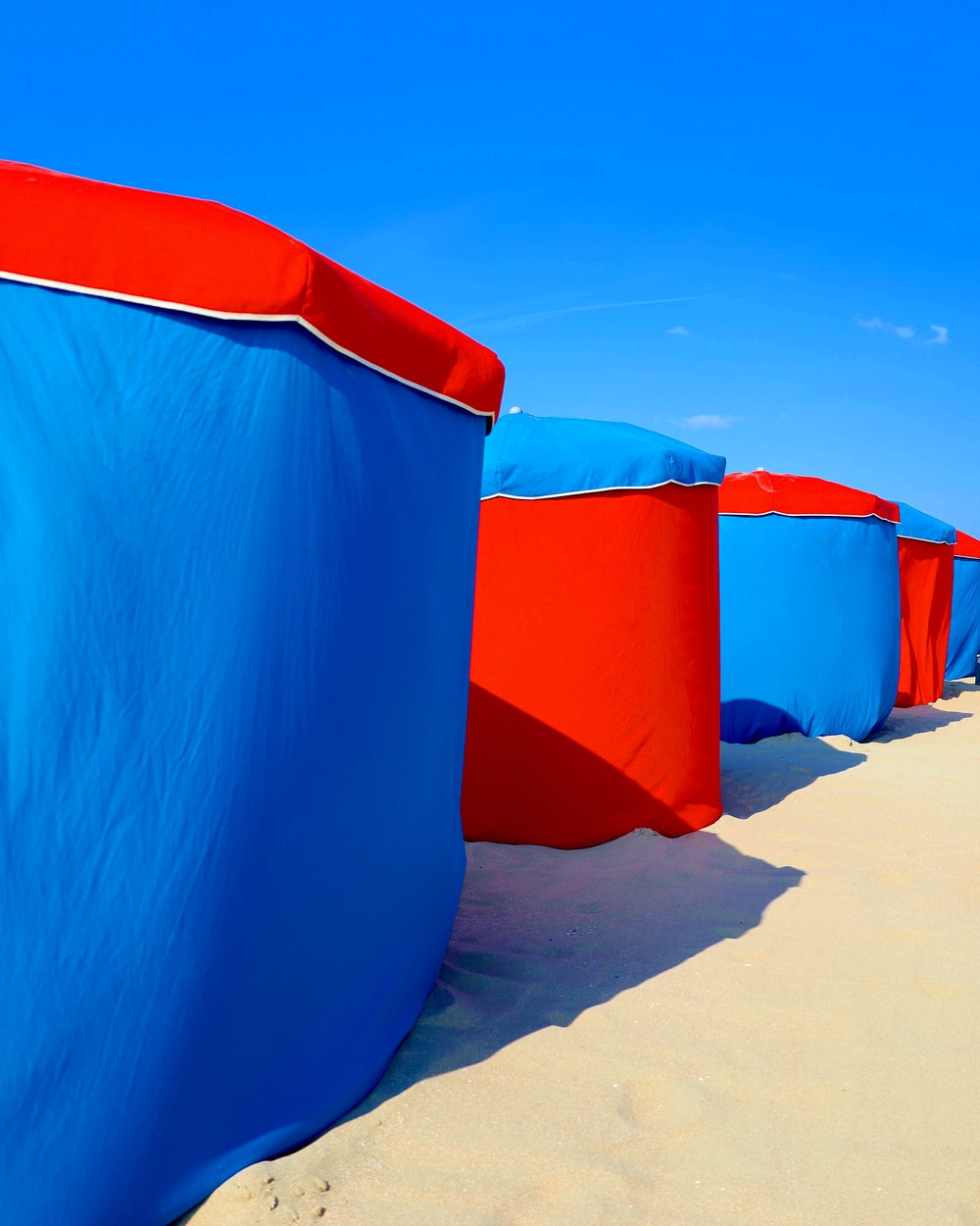 blue and red inflatable tent on brown sand during daytime