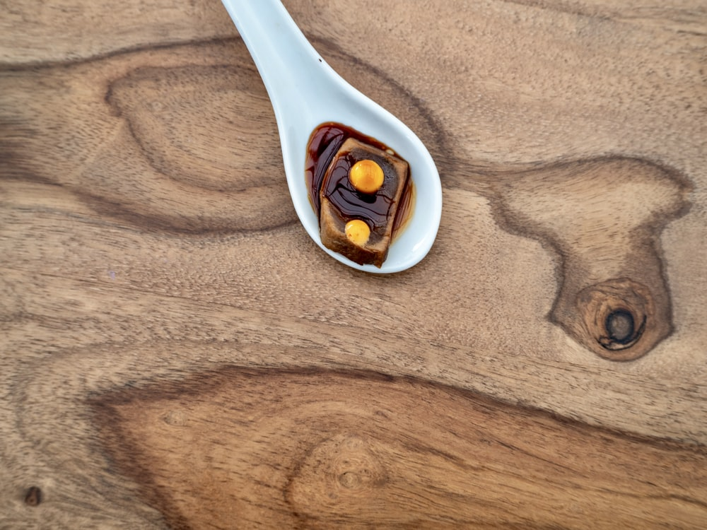 white plastic spoon on brown wooden table