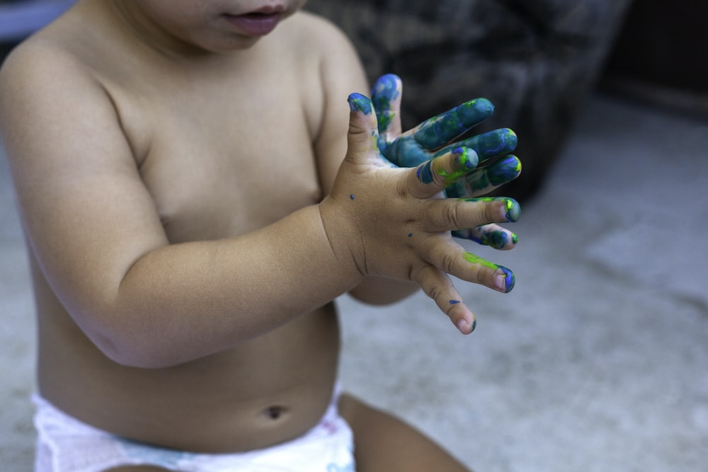 topless child with green manicure