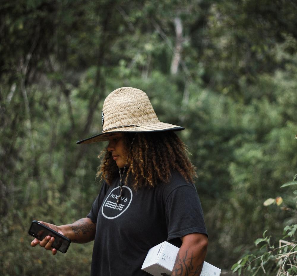 woman in black crew neck t-shirt holding black smartphone