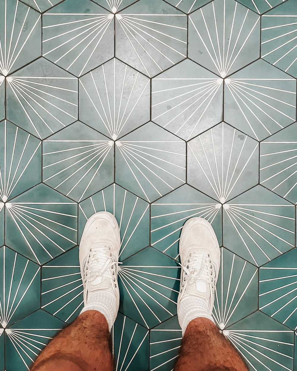 person wearing white shoes standing on white and brown floor tiles