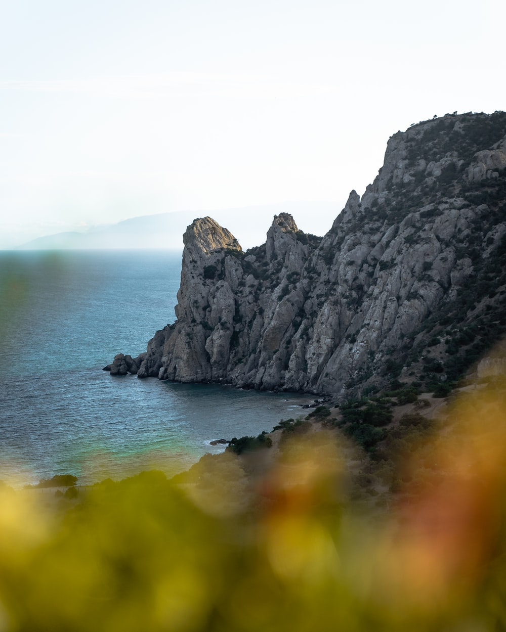 gray rocky mountain beside body of water