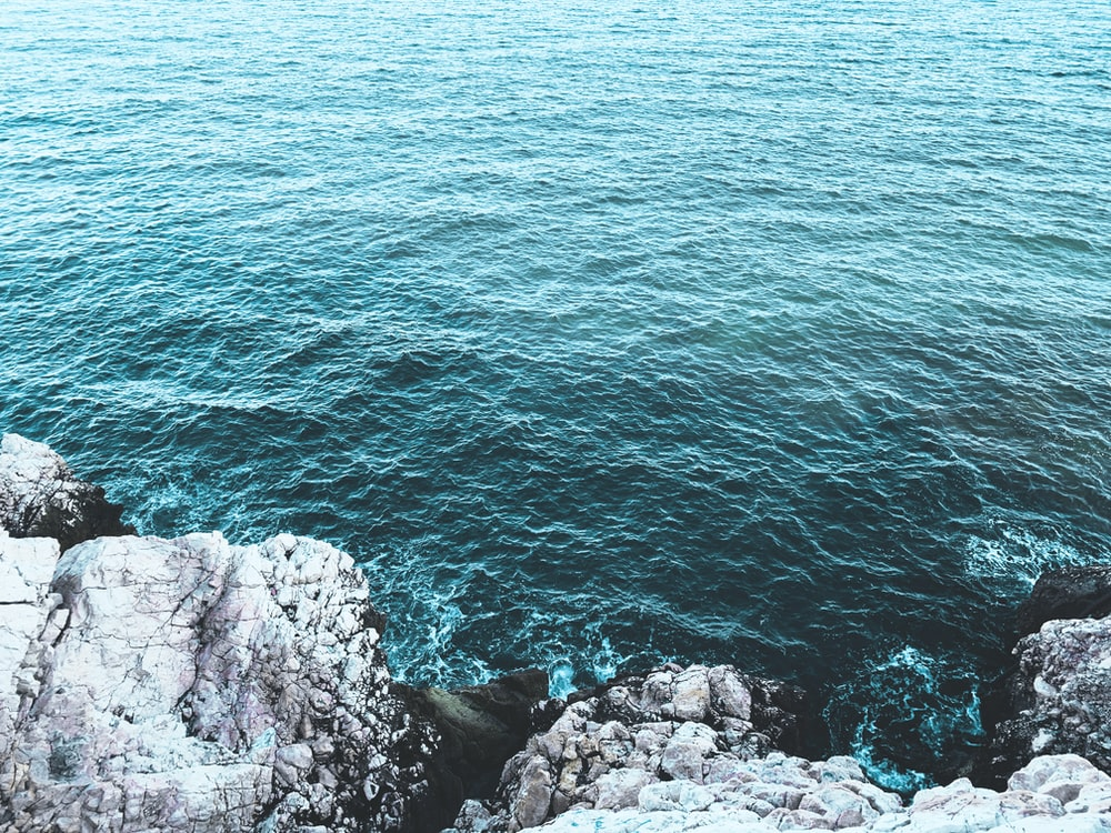 gray rocky shore with blue water