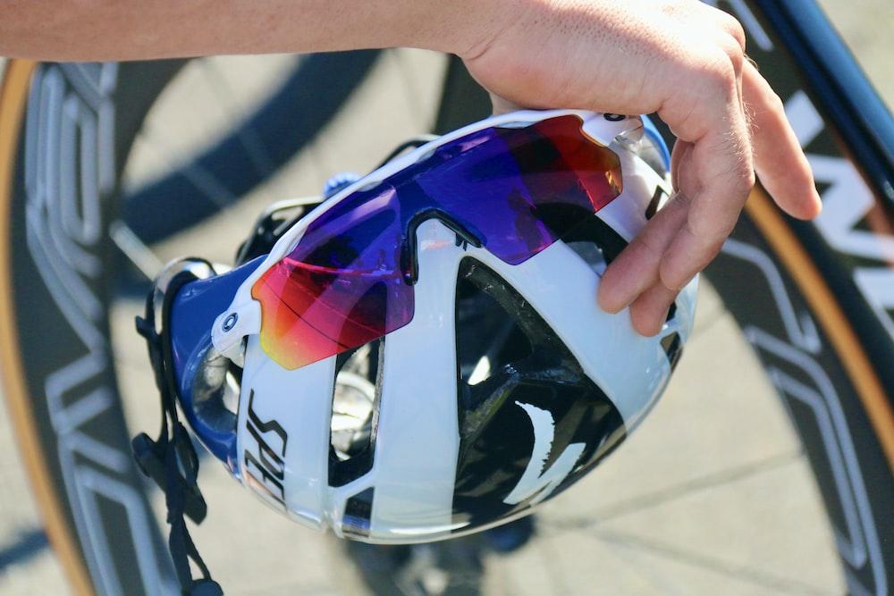blue and black helmet on hand