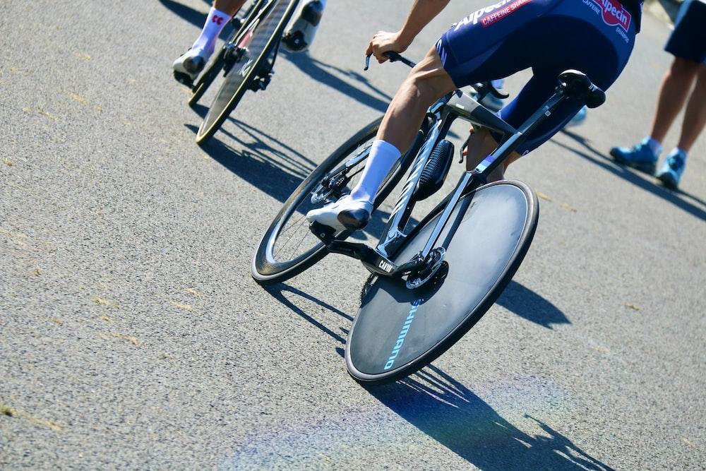 man in blue shirt riding on bicycle during daytime