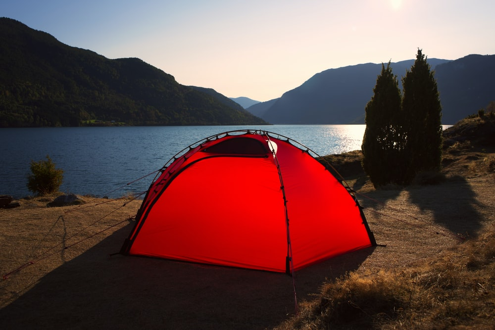 red dome tent near body of water during daytime