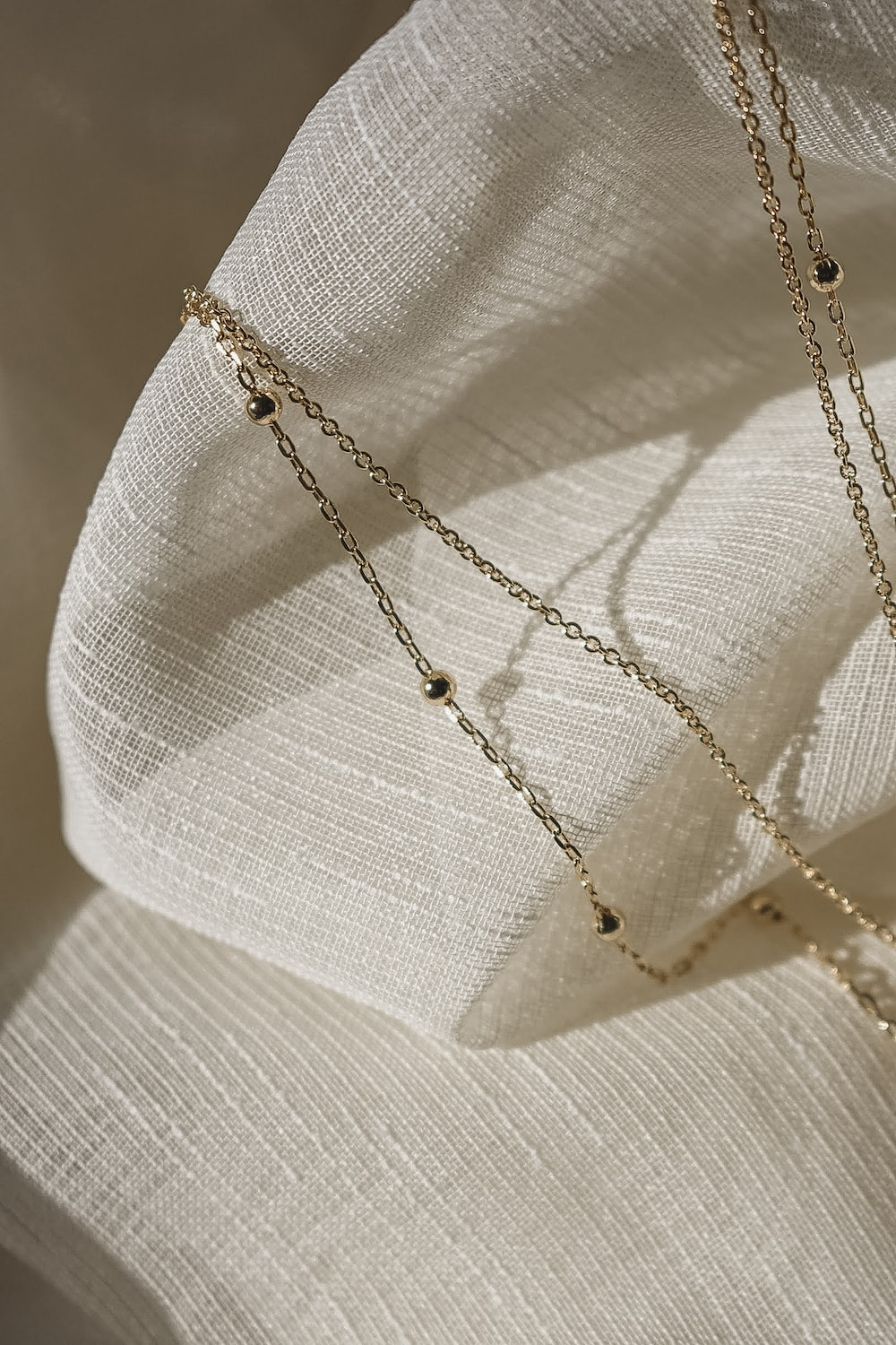 silver necklace on white textile