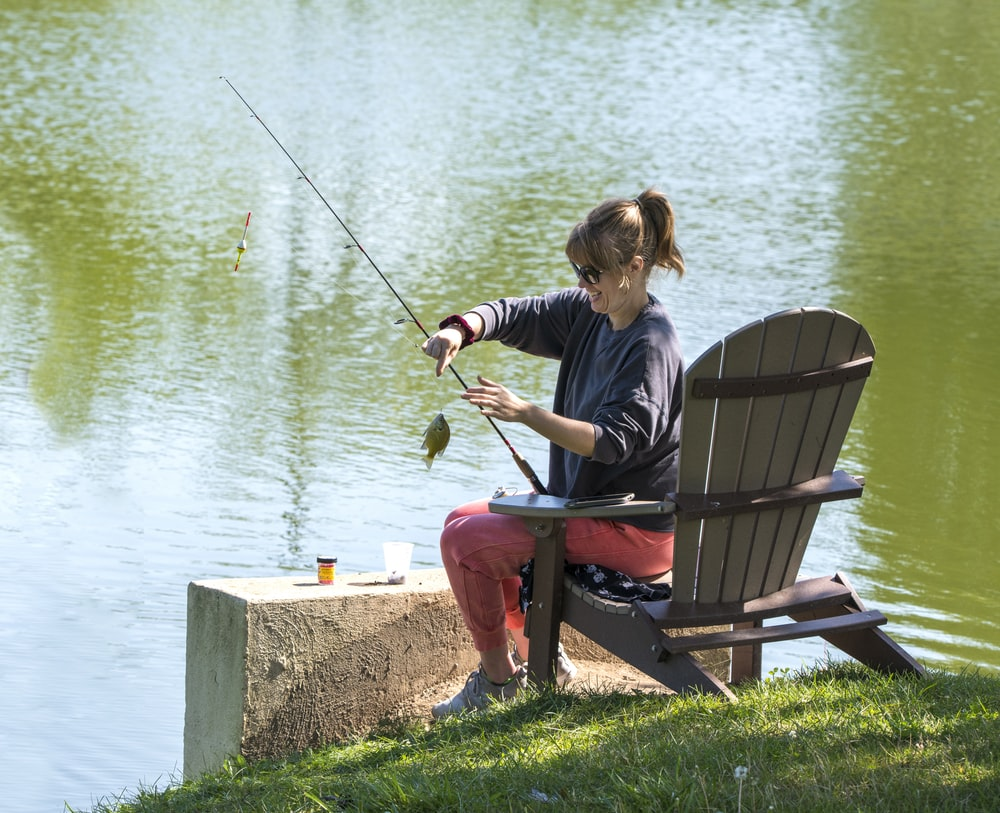 woman in blue shirt and black pants sitting on brown wooden bench while fishing during daytime