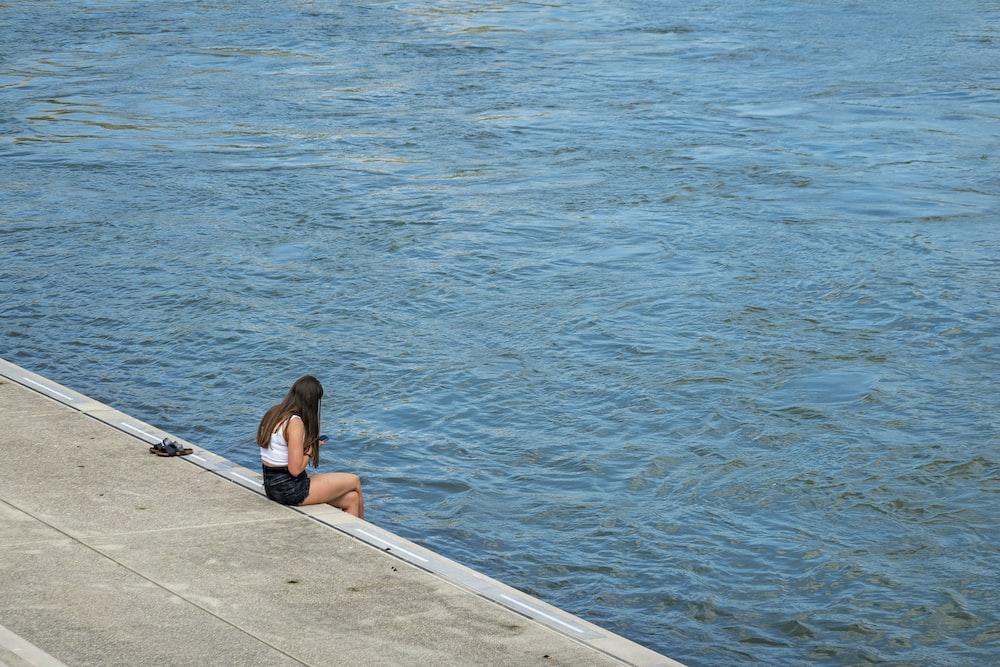 woman in black bikini sitting on dock near body of water during daytime