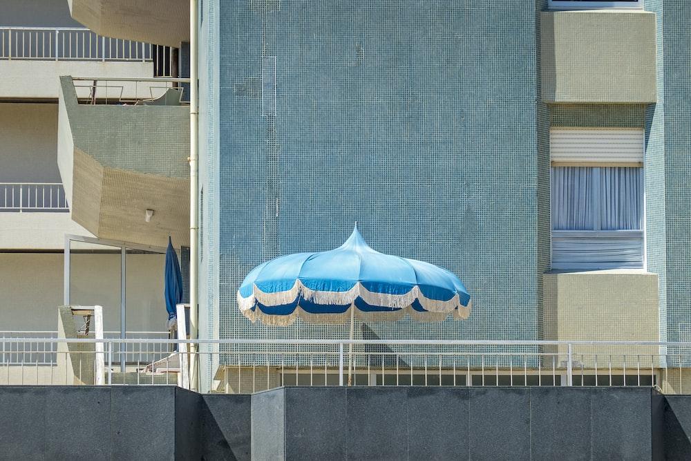 blue and white umbrella on gray concrete wall