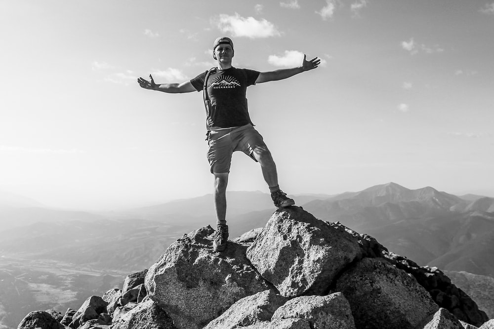 man in black tank top and white shorts standing on rock formation during daytime
