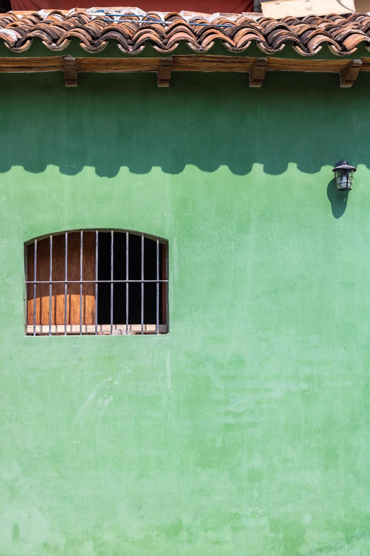 black metal window frame on green concrete wall