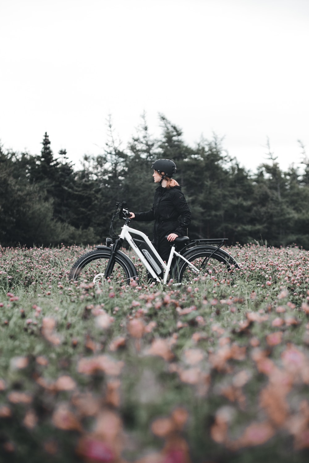 man in black jacket riding on bicycle on green grass field during daytime