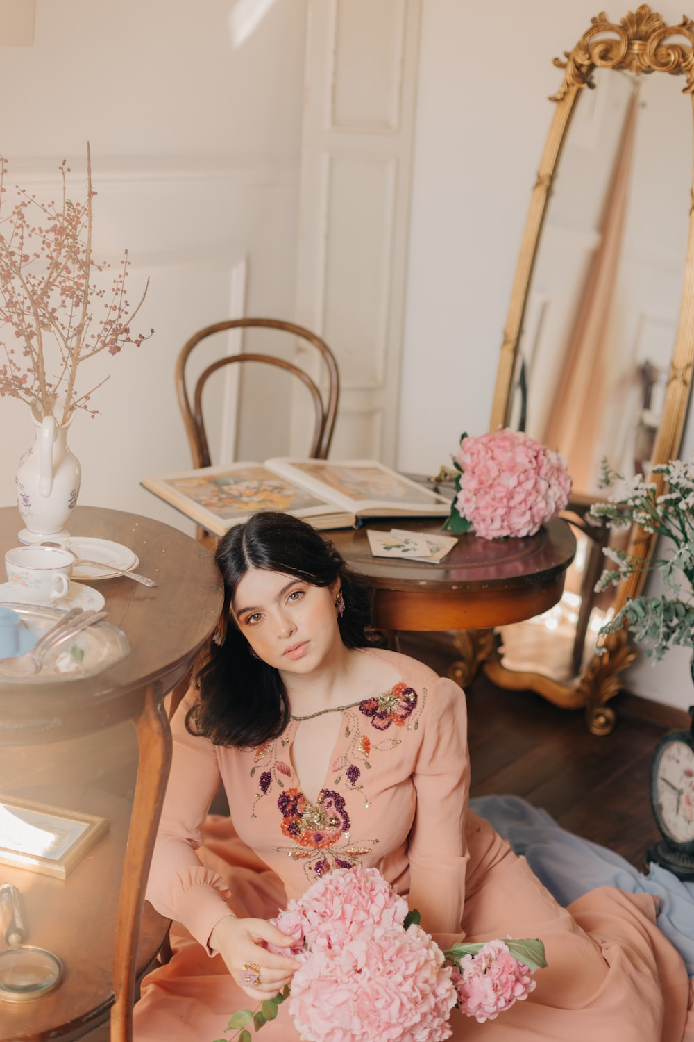 woman in pink and white floral dress sitting on chair