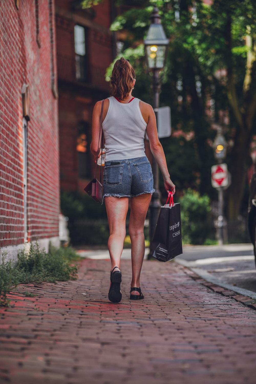 woman in white tank top and blue denim shorts walking on sidewalk during daytime