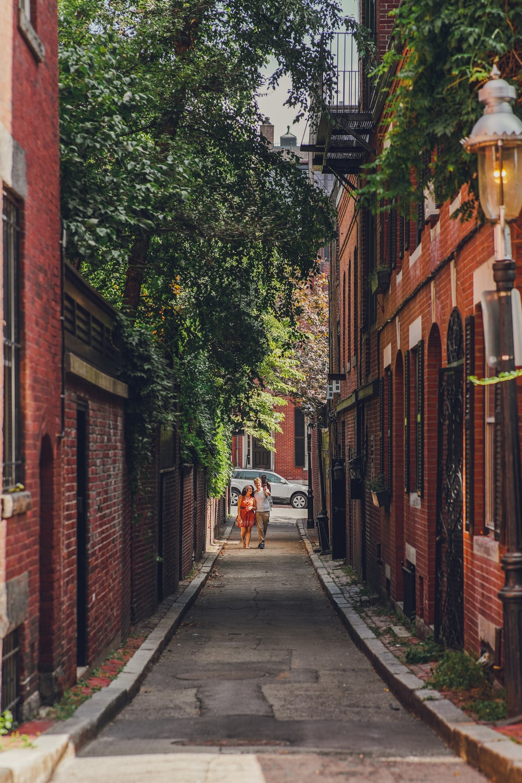 man in white shirt and black pants walking on sidewalk during daytime