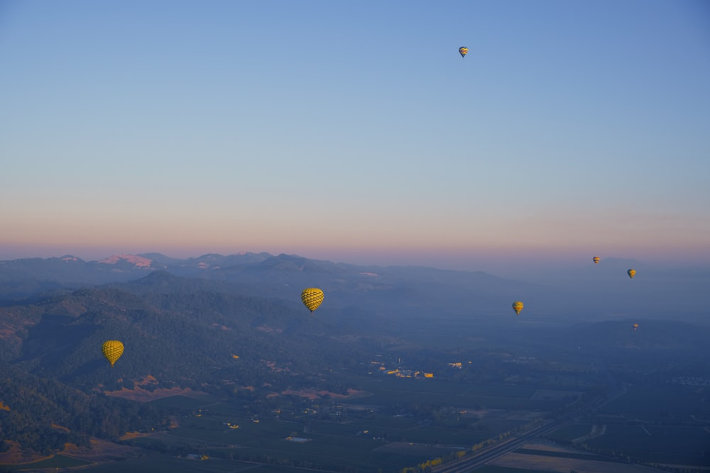 hot air balloons flying over green mountains during daytime