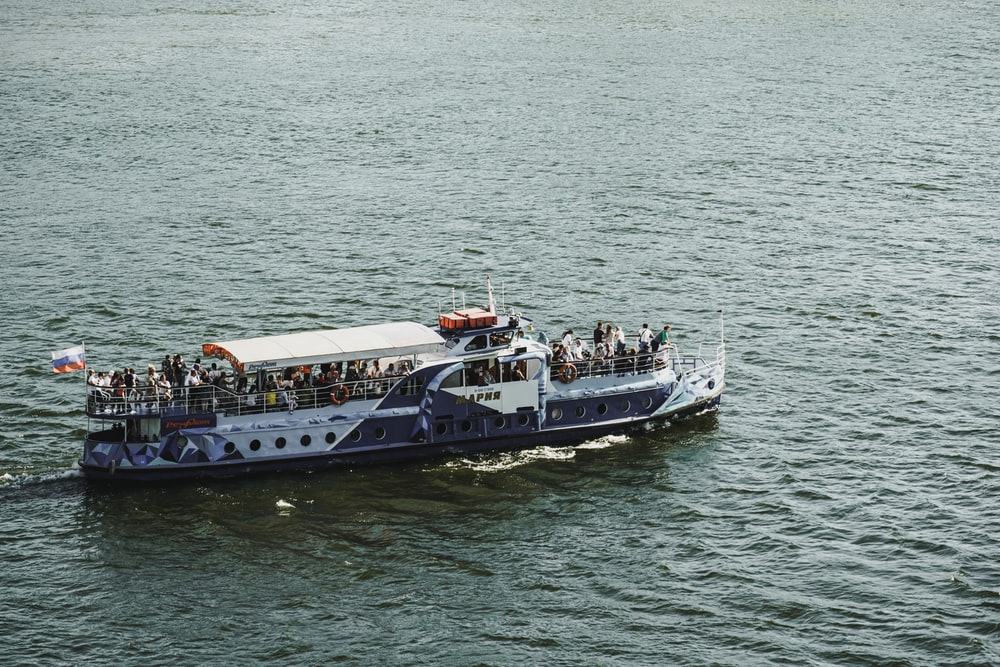 people riding on white boat on sea during daytime