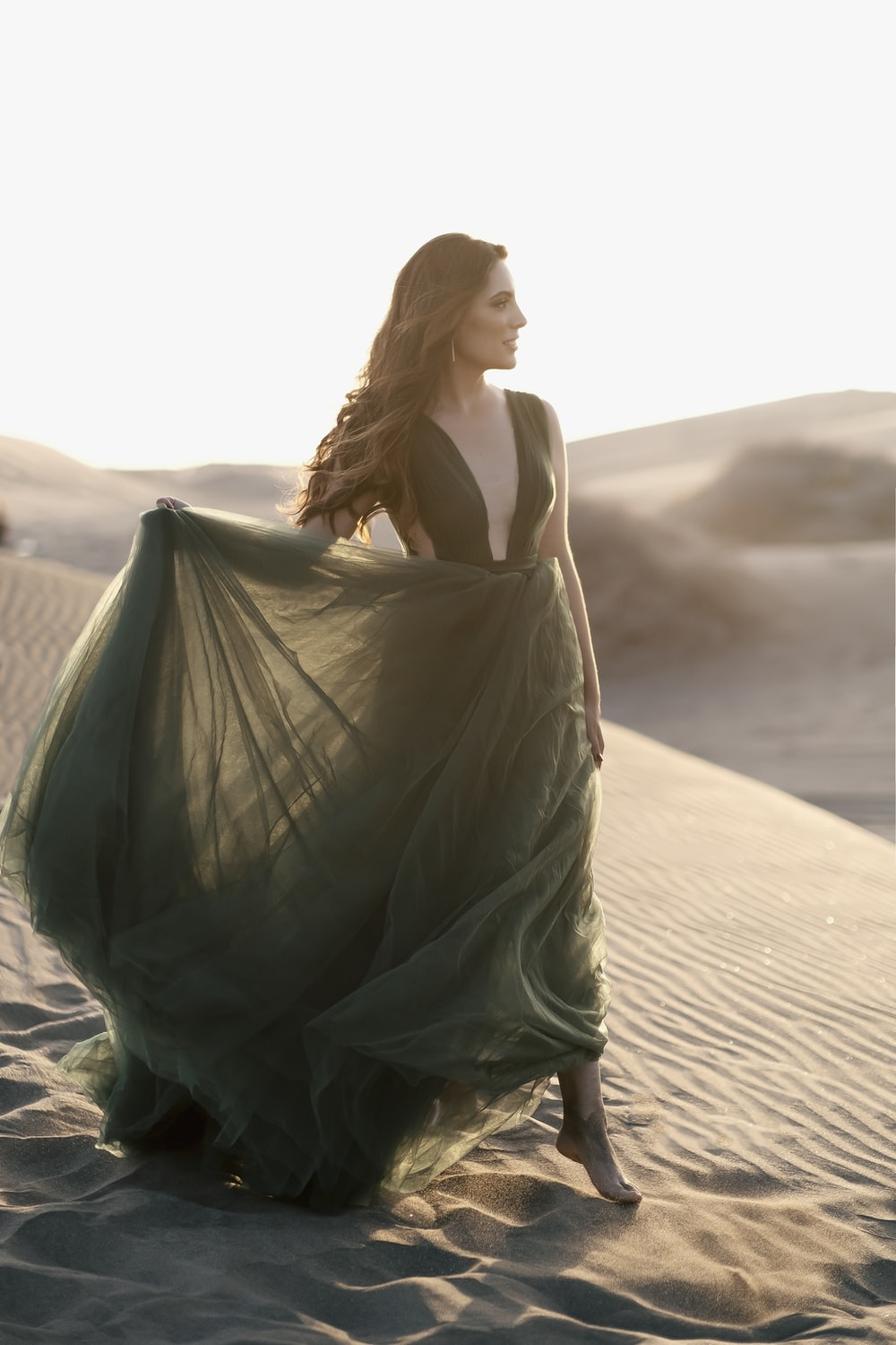 woman in green dress standing on brown sand during daytime