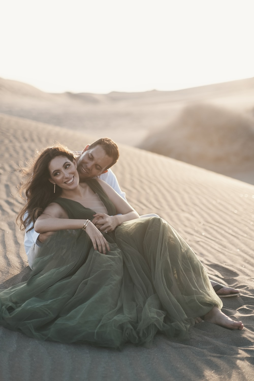 woman in blue dress hugging man in white shirt on desert during daytime