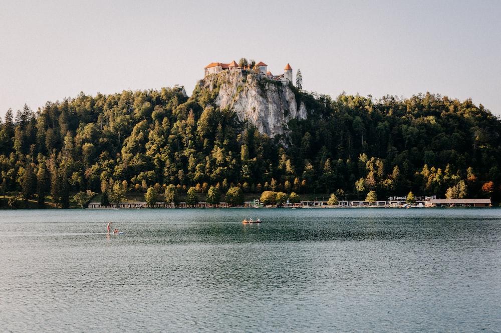 people riding boat on lake near brown mountain during daytime