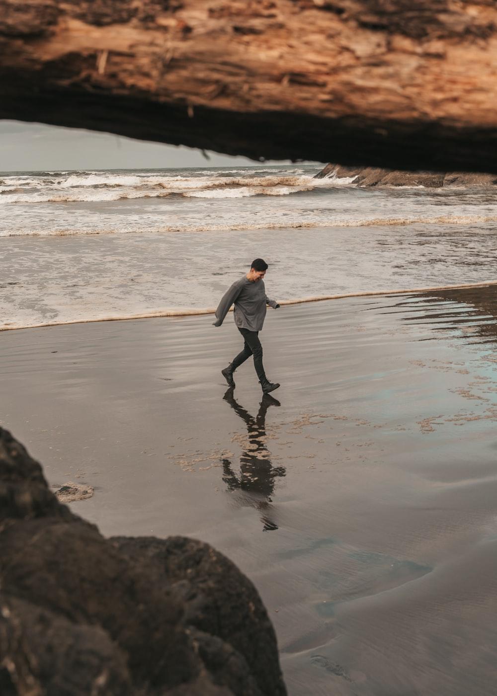 man in gray jacket and black pants walking on seashore during daytime