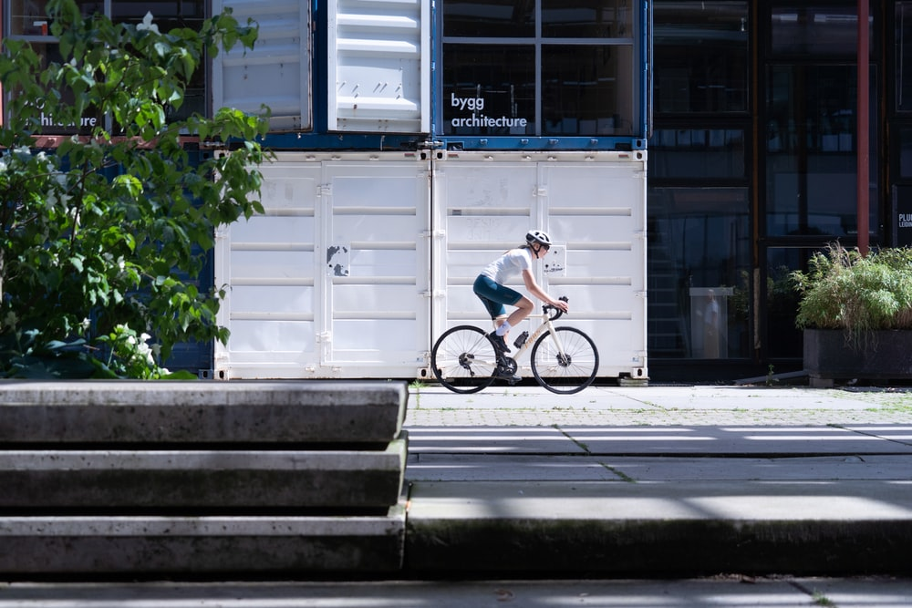 man in blue shirt riding bicycle on gray concrete stairs during daytime