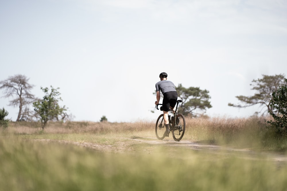 man in black jacket riding bicycle on green grass field during daytime