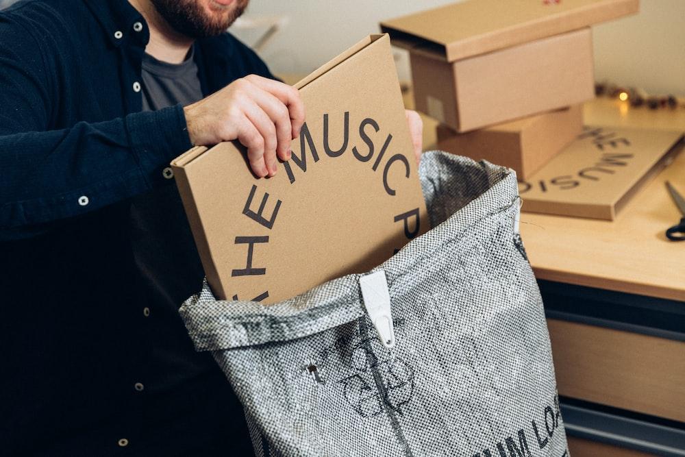 man in black jacket holding brown cardboard box
