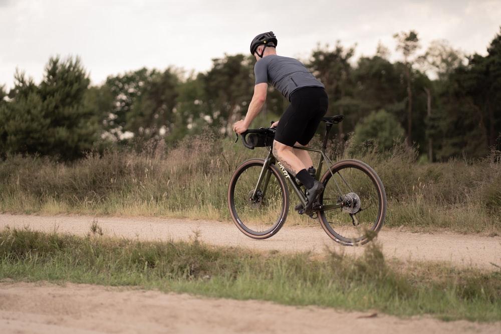 man in black t-shirt riding black mountain bike on brown field during daytime