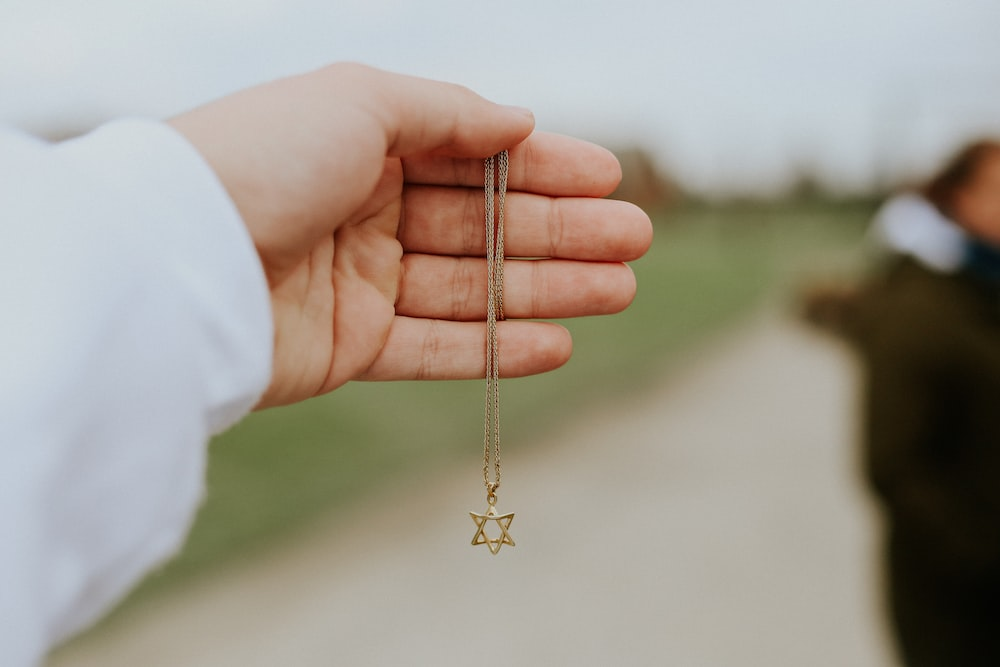 person holding gold cross pendant necklace