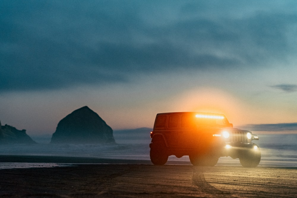 orange truck on beach during sunset