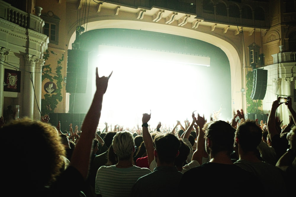 people raising their hands in front of white curtain