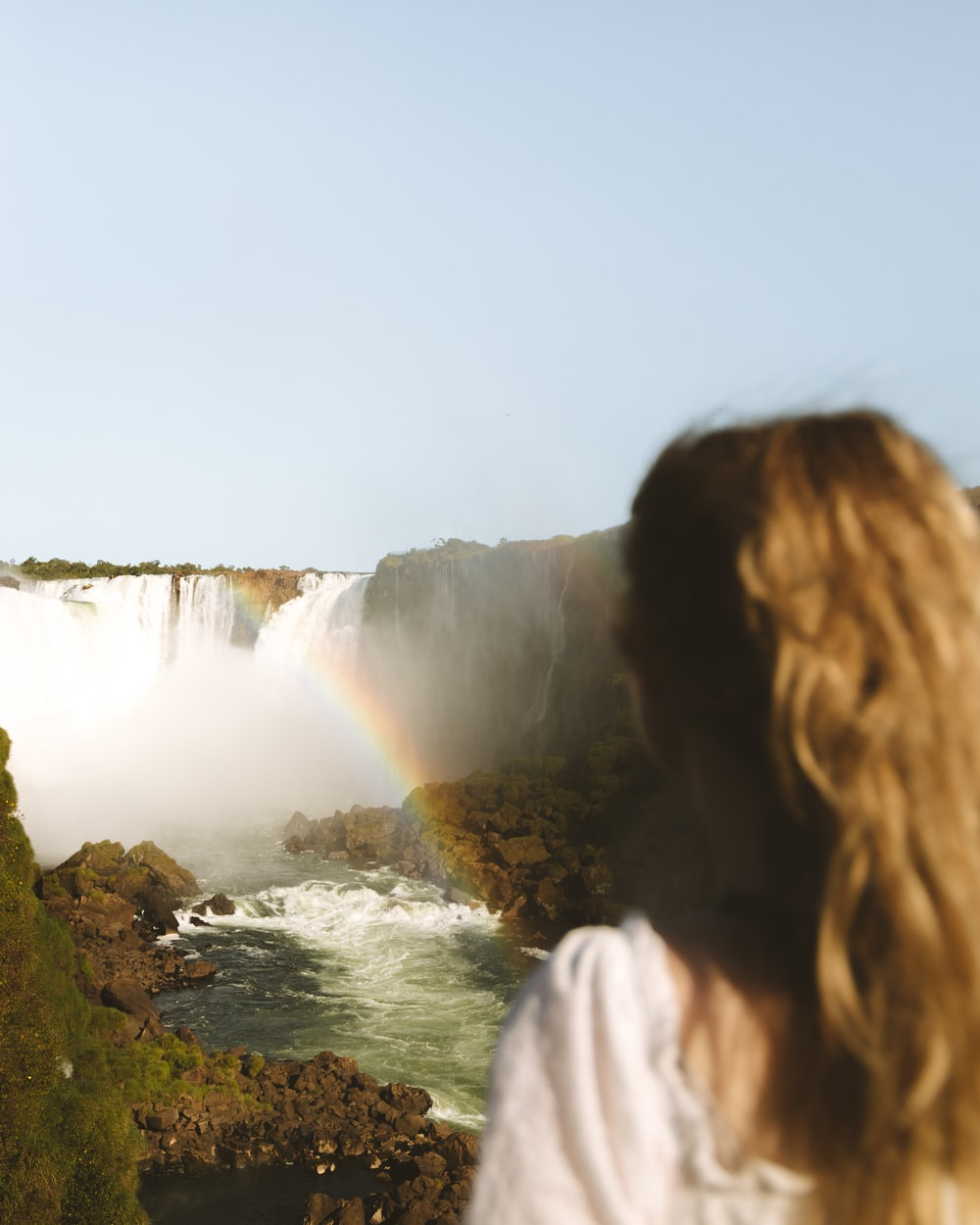woman in white shirt standing on green grass near waterfalls during daytime