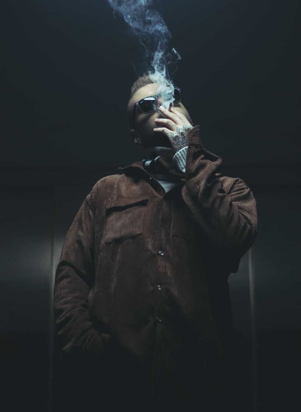 man in brown leather jacket smoking cigarette